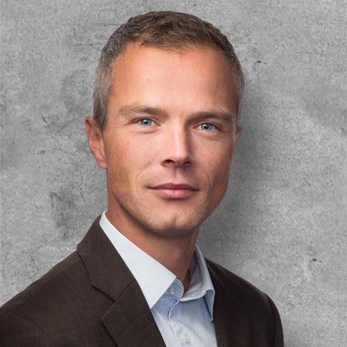 zakelijke portretfoto amsterdam tegen ingemonteerde betonnen achtergrond